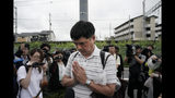 """A man prays for the victims of Thursday's fire at the Kyoto Animation Studio building, Friday, July 19, 2019, in Kyoto, Japan. A man screaming """"You die!"""" burst into the animation studio in Kyoto, doused it with a flammable liquid and set it on fire Thursday, killing dozens of people in the attack that shocked the country and brought an outpouring of grief from anime fans. (AP Photo/Jae C. Hong)"""