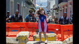 A girl wearing a dress featuring the Puerto Rican flag stands by police blocking the road leading to the La Fortaleza governors mansion in San Juan, Puerto Rico, Thursday, July 18, 2019. Protesters are demanding Gov. Ricardo Rossello resign after the leak of online chats that show him making misogynistic slurs and mocking his constituents. (AP Photo/Dennis M. Rivera Pichardo)