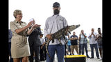 Florida alligator expert Frank Robb receives a round of applause as he holds an alligator during a news conference, Tuesday, July 16, 2019, in Chicago. Robb captured the elusive alligator in a public lagoon at Humboldt Park early Tuesday. At left is Kelley Gandurski, executive director of Chicago Animal Care and Control. (AP Photo/Amr Alfiky)