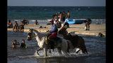 Un hombre ofrece montar a caballo a turistas en una playa a las afueras de La Habana el jueves 18 de julio de 2019. (AP Foto/Ramon Espinosa)