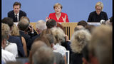 German Chancellor Angela Merkel, rear center, addresses the media during her annual sommer press conference in Berlin, Germany, Friday, July 19, 2019. (AP Photo/Michael Sohn)