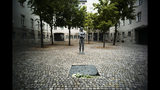 In this Friday, July 12, 2019 photo a sculpture and a remembrance plaque placed in the courtyard of the Bendlerblock building of the German defensive ministry where the German Resistance Memorial Center is located, in Berlin. Several leaders of the failed assassinate to Adolf Hitler on July 20, 1944 was shoot dead in the courtyard. The inscription reads: 'You did not bear the shame, you defend yourself, you gave the big eternal watch, a sign of repentance, your sacrificing your hot life for freedom right and honor'. (AP Photo/Markus Schreiber)