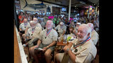 In this photo provided by the Florida Keys News Bureau, former winners of the Hemingway Look-Alike contest, including Charlie Boice, right, evaluate 2019 entrants Thursday, July 18, 2019, at Sloppy Joe's Bar in Key West, Fla. The competition, that has attracted about 135 entrants, is part of the island city's annual Hemingway Days festival that pays homage to Ernest Hemingway who lived and wrote in Key West in the 1930s. (Andy Newman/Florida Keys News Bureau via AP)