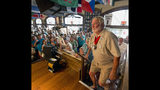 In this photo provided by the Florida Keys News Bureau, Jerry Jerele climbs to the stage at Sloppy Joe's Bar to compete in the Hemingway Look-Alike Contest, Thursday, July 18, 2019, in Key West, Fla. The competition, that has attracted about 135 entrants, is part of the island city's annual Hemingway Days festival that honors Ernest Hemingway who lived and wrote in Key West in the 1930s. (Andy Newman/Florida Keys News Bureau via AP)