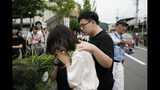 """A woman prays to honor the victims of Thursday's fire at the Kyoto Animation Studio building, Friday, July 19, 2019, in Kyoto, Japan. A man screaming """"You die!"""" burst into the animation studio in Kyoto, doused it with a flammable liquid and set it on fire Thursday, killing dozens of people in the attack that shocked the country and brought an outpouring of grief from anime fans. (AP Photo/Jae C. Hong)"""