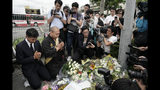 """Japanese Diet member, Kenta Izumi, left, and Buddhist monk, Matsumoto Genkun, pay respects at a makeshift memorial site in front of burned Kyoto Animation Studio building, background left, Friday, July 19, 2019, in Kyoto, Japan. A man screaming """"You die!"""" burst into the animation studio in Kyoto, doused it with a flammable liquid and set it on fire Thursday, killing dozens of people in the attack that shocked the country and brought an outpouring of grief from anime fans. (AP Photo/Jae C. Hong)"""