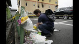 """A man places flowers outside the Kyoto Animation Studio building consumed in an arson attack, Friday, July 19, 2019, in Kyoto, Japan. A man screaming """"You die!"""" burst into the animation studio in Kyoto, doused it with a flammable liquid and set it on fire Thursday, killing dozens of people in the attack that shocked the country and brought an outpouring of grief from anime fans. (AP Photo/Jae C. Hong)"""