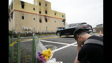 """A man prays for the victims after placing flowers outside the Kyoto Animation Studio building consumed in an arson attack, Friday, July 19, 2019, in Kyoto, Japan. A man screaming """"You die!"""" burst into the animation studio in Kyoto, doused it with a flammable liquid and set it on fire Thursday, killing dozens of people in the attack that shocked the country and brought an outpouring of grief from anime fans. (AP Photo/Jae C. Hong)"""