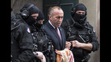 FILE - In this Thursday, Jan. 12, 2017 file photo, Former Prime Minister of Kosovo Ramush Haradinaj, center, leaves the court escorted by hooded police officers in Colmar, eastern France. Kosovo's prime minister has resigned from the post after he has been invited to be questioned from a European Union-funded court investigating crimes against ethnic Serbs during and after the 1998-99 independence war with Serbia. Haradinaj said on Friday, July 19, 2019 he had informed the Cabinet of his resignation and urged the country's president to set a date for an early parliamentary election. (AP Photo/Jean-Francois Badias)