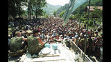 FILE - In this July 13, 1995 file photo, Dutch U.N. peacekeepers sit on top of an armored personnel carrier while Muslim refugees from Srebrenica, eastern Bosnia, gather in the village of Potocari, just north of Srebrenica. The Dutch Supreme Court is ruling Friday July 19, 2019 in a long-running legal battle over whether the Netherlands can be held liable in the deaths of more than 300 Muslim men who were murdered by Bosnian Serb forces during the 1995 Srebrenica massacre. (AP Photo/File)