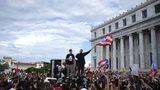 El rapero puertorriqueño René Juan Pérez, conocido como Residente, y Benito Antonio Martínez Ocasio, cuyo nombre artístico es Bad Bunny, animan a manifestantes frente al Capitolio antes de una marcha contra el gobernador Ricardo Rosselló, en San Juan, Puerto Rico, el miércoles 17 de julio de 2019. (AP Foto/Dennis M. Rivera Pichardo)