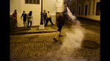 A demonstrator returns a tear gas canister during clashes in San Juan, Puerto Rico, Wednesday, July 17, 2019. Thousands of people marched to the governor's residence in San Juan on Wednesday chanting demands for Gov. Ricardo Rossello to resign after the leak of online chats that show him making misogynistic slurs and mocking his constituents. (AP Photo / Carlos Giusti)