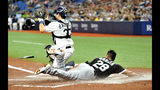 Tampa Bay Rays catcher Travis d'Arnaud waits for the throw as Chicago White Sox's Leury Garcia (28) loses his helmet and scores on Jose Abreu's RBI-single during the first inning of a baseball game Friday, July 19, 2019, in St. Petersburg, Fla. (AP Photo/Steve Nesius)