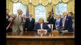 El presidente Donald Trump, acompañado por los astronautas Michael Collins, izquierda, y Buzz Aldrin, derecha, del Apolo 11, así como por el vicepresidente Mike Pence y la primera dama Melania Trump, escucha durante una reunión para conmemorar el 50mo aniversario del alunizaje del Apolo 11, en la Oficina Oval de la Casa Blanca, el viernes 19 de julio de 2019, en Washington. (AP Foto/Alex Brandon)