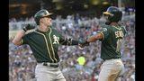 El jugador de los Atléticos de Oakland Mark Canha, a la izquierda, y Marcus Semien celebran un jonrón de dos carreras de Canha ante el pitcher de los Mellizos de Minnesota Zack Littell, en el séptimo inning de su juego de béisbol el sábado 20 de julio de 2019 en Minneapolis. (AP Foto/Jim Mone)