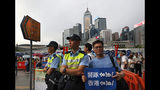 """CORRECTS TRANSLATION - A man poses with a picture next to police officers with a placard reads"""" Go Police ! """" during a counter-rally in support of the police in Hong Kong Saturday, July 20, 2019. A counter-rally in support of the police was held Saturday evening. Thousands of people under umbrellas and overcast skies filled a park in central Hong Kong. (AP Photo/Vincent Yu)"""