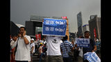 """CORRECTS TRANSLATION - Pro-China supporters raises a placard reads"""" Go Police !"""" during a counter-rally in support of the police in Hong Kong Saturday, July 20, 2019. Police in Hong Kong have raided a homemade-explosives manufacturing lab ahead of another weekend of protests in the semi-autonomous Chinese territory. (AP Photo/Vincent Yu)"""