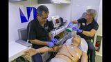 In this Monday, July 15, 2019, photo Shanti Fernandez, 32, a recent nursing graduate, performs a checkup on HAL, a medical manikin, at the Miami Dade medical campus in Miami. (Matias J. Ocner/Miami Herald via AP)