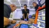 In this Monday, July 15, 2019, photo from left, Jesus Sola, 50, Mario Alem, 57, and Michael Yoder, 60, perform chest compressions on a medical manikin inside a simulated ambulance at the Miami Dade College medical campus in Miami. (Matias J. Ocner/Miami Herald via AP)