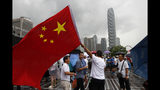 A pro-China supporter waves a Chinese national flag during a counter-rally in support of the police in Hong Kong Saturday, July 20, 2019. Police in Hong Kong have raided a homemade-explosives manufacturing lab ahead of another weekend of protests in the semi-autonomous Chinese territory.(AP Photo/Vincent Yu)