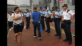 A woman shows thumps up to police officers during a counter-rally in support of the police in Hong Kong Saturday, July 20, 2019. A counter-rally in support of the police was held Saturday evening. Thousands of people under umbrellas and overcast skies filled a park in central Hong Kong. (AP Photo/Vincent Yu)