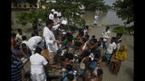 Medical officers distribute medicines to flood victims in Gagalmari, in the northeastern Indian state of Assam, Friday, July 19, 2019. In the Indian state of Assam, officials said floodwaters have killed more than a dozen people and brought misery to some 4.5 million. (AP Photo/Anupam Nath)