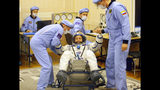 Russian Space Agency experts help U.S. astronaut Andrew Morgan, member of the main crew of the expedition to the International Space Station (ISS), to stand up after inspecting his space suit prior the launch of Soyuz MS-13 space ship at the Russian leased Baikonur cosmodrome, Kazakhstan, Saturday, July 20, 2019. (AP Photo/Dmitri Lovetsky, Pool)