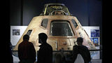 Visitors look at the NASA Apollo 11 command module Columbia, the centerpiece of Destination Moon: The Apollo 11 Mission exhibit at the Museum of Flight, Friday, July 19, 2019, in Seattle. The module functioned as a mother ship, carrying the crew of three astronauts and the second Apollo spacecraft, the lunar module, to orbit around the moon, and brought the astronauts back to Earth. The exhibit commemorates the historic landing by American astronauts on the moon 50 years earlier, on July 20, 1969. (AP Photo/Elaine Thompson)