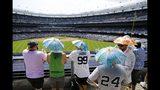Fanáticos de los Yanquis con paraguas para taparse del sol durante el sexto inning del juego entre los Yanquis de Nueva York y los Rockies de Colorado, el sábado 20 de julio de 2019. (AP Foto/Frank Franklin II)