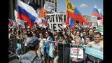 People with Russian and party flags gather during a protest in Moscow, Russia, Saturday, July 20, 2019. People have gathered in central Moscow to demand that opposition candidates be included on ballots for an upcoming city parliament election in September. (AP Photo/Pavel Golovkin)