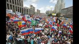 People with national flags and various political party flags gather during a protest in Moscow, Russia, Saturday, July 20, 2019. Masses of people gathered in central Moscow to demand that opposition candidates be included on ballots for an upcoming city parliament election in September. (AP Photo/Pavel Golovkin)