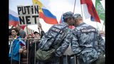 """Rosguardia (National Guard) soldiers talk as people with Russian and various political party flags protest, with a man holding sign reading """"Putin No!"""" in Moscow, Russia, Saturday, July 20, 2019. Masses of people gathered in central Moscow to demand that opposition candidates be included on ballots for an upcoming city parliament election in September. (AP Photo/Pavel Golovkin)"""