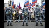 """People with Russian and various political party flags stand in front of police line, with small signs reading """"I have the right to choose"""", during a protest in Moscow, Russia, Saturday, July 20, 2019. Masses of people gathered in central Moscow to demand that opposition candidates be included on ballots for an upcoming city parliament election in September. (AP Photo/Pavel Golovkin)"""