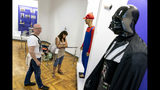 "In this photo taken on Friday, July 12, 2019, visitors walk past a mannequin of Darth Vader, on display in an exhibition at the National History Museum, in Kiev, Ukraine. A Darth Vader costume, playground equipment, pastries and boxes of food all are part of an exhibit at Ukraine's National History Museum displaying the colorful behavior and sometime-questionable practices that characterize the country's elections. The exhibition, called ""The Museum of Election Trash"" was put together ahead of the snap parliamentary elections on Sunday, July 21, 2019. (AP Photo/Evgeniy Maloletka)"