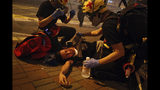 Medical workers help a protester in pain from tear gas fired by policemen on a street in Hong Kong, Sunday, July 21, 2019. Hong Kong police have thrown tear gas canisters at protesters after they refused to disperse. Hundreds of thousands of people took part in a march Sunday to call for direct elections and an independent investigation into police tactics used during earlier pro-democracy demonstrations. Police waved a black warning flag Sunday night before lobbing the canisters into a crowd of protesters. (AP Photo/Bobby Yip)