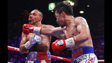 Manny Pacquiao, right, lands a punch against Keith Thurman in the fifth round during a welterweight title fight Saturday, July 20, 2019, in Las Vegas. (AP Photo/John Locher)