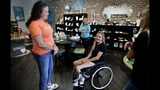 In this Monday, July 8, 2019 photo, Izzy Kitterman, center, 15, speaks with Vintage Pearl employee June Anne Wakley, left, as employee Angela Olson works on the Izzy K Collection displayed in the background in Tulsa, Okla. Kitterman was injured in a 2017 crash near Purcell, Okla., after an outing with soccer friends, and the jewelry line will help fund her rehabilitation. (Mike Simons/Tulsa World via AP)
