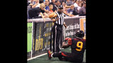 In this Saturday, May 25, 2013 photo, fans participate as Predators fullback Marlon Moye-Moore flips the ball to a fan who is leaning over the field during the Jacksonville Sharks at Orlando Predators Arena League Football game at the Amway Center in Orlando, Fla. Moye-Moore, 39, spent nine seasons in the Arena Football League, all with the Predators. Moye-Moore has been a firefighter now for slightly more than a year. (Stephen M. Dowell/Orlando Sentinel via AP)