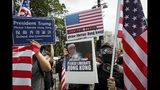 """Manifestantes mostrando una pancarta con banderas estadounidenses y la imagen del presidente de Estados Unidos y la frase """"Presidente Trump, por favor, libere Hong Kong, durante una marcha en el Parque Victoria de Hong Kong, el domingo 21 de julio de 2019. (AP Foto/Vincent Yu)"""