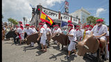 """In this photo provided by the Florida Keys News Bureau, Ernest Hemingway look-alikes make the turn at Sloppy Joe's Bar during the """"Running of the Bulls"""" Saturday, July 20, 2019, in Key West, Fla. Held on the eve of the 120th anniversary of Hemingway's birth, the whimsical takeoff on the famed run in Pamplona, Spain, was a facet of the island city's annual Hemingway Days festival that ends Sunday, July 21. Hemingway lived and wrote in Key West throughout most of the 1930s. (Andy Newman/Florida Keys News Bureau via AP)"""