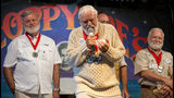 In this Saturday, July 20, 2019, photo provided by the Florida Keys News Bureau, Dusty Rhodes, center, urges judges at the Hemingway Look-Alike Contest to select him the winner of the 2019 competition at Sloppy Joe's Bar in Key West, Fla. The contest, that attracted 142 entrants, highlighted activities during the yearly Hemingway Days festival that honors author Ernest Hemingway who lived in Key West during the 1930s. (Andy Newman/Florida Keys News Bureau via AP)