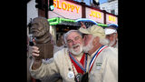 In this Saturday, July 20, 2019, photo provided by the Florida Keys News Bureau, Joe Maxey, left, gets a playful smooch from Michael Groover, after Maxey won the Hemingway Look-Alike Contest at Sloppy Joe's Bar in Key West, Fla. Competing for his eighth time, Maxey beat 141 other contestants to claim top honors. Groover, husband of celebrity chef Paula Deen, won the title in 2018. (Andy Newman/Florida Keys News Bureau via AP)