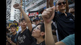Protesters gestures during a march on a street in Hong Kong, Sunday, July 21, 2019. Thousands of Hong Kong protesters marched from a public park to call for an independent investigation into police tactics. (AP Photo/Vincent Yu)