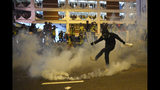 A protestor kicks a tear gas canister during confrontation in Hong Kong Sunday, July 21, 2019. Hong Kong police launched tear gas at protesters Sunday after a massive pro-democracy march continued late into the evening. The action was the latest confrontation between police and demonstrators who have taken to the streets to protest an extradition bill and call for electoral reforms in the Chinese territory. (Ming Ko/HK01 via AP)