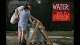 Pitchfork attendees get water at a station during an excessive heat wave in the Chicago area on Saturday, July 20, 2019. (Camille Fine/Chicago Tribune via AP)
