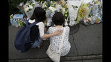 Two women pay their respects at a makeshift memorial to honor the victims of Thursday's fire at the Kyoto Animation Studio building, Saturday, July 20, 2019, in Kyoto, Japan. The man suspected of setting ablaze a beloved Japanese animation studio was raging about theft and witnesses and media reported he had a grudge against the company, as questions arose why such mass killings keep happening in the country.(AP Photo/Jae C. Hong)