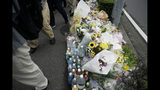 Pedestrians walk past a makeshift memorial set up to honor the victims of Thursday's fire at the Kyoto Animation Studio building, Saturday, July 20, 2019, in Kyoto, Japan. The man suspected of setting ablaze a beloved Japanese animation studio was raging about theft and witnesses and media reported he had a grudge against the company, as questions arose why such mass killings keep happening in the country. (AP Photo/Jae C. Hong)