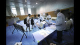 Representatives of a local election administration commission show two earliest voters the empty ballot box before they cast their votes for the upper house elections at a polling station in Tokyo Sunday, July 21, 2019. Voting started Sunday morning for the upper house elections where Japanese Prime Minister Shinzo Abe's ruling coalition is seen to retain majority, according to local media report. (AP Photo/Eugene Hoshiko)