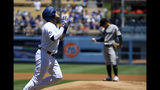 Los Angeles Dodgers' Max Muncy, left, gestures before scoring after hitting a solo home run as Miami Marlins starting pitcher Jordan Yamamoto stands on the mound during the first inning of a baseball game Sunday, July 21, 2019, in Los Angeles. (AP Photo/Mark J. Terrill)