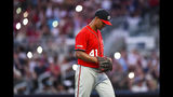 Washington Nationals' Joe Ross walks to the dugout under dimmed stadium lights while being relieved in the sixth inning of a baseball game against the Atlanta Braves, Sunday, July 21, 2019, in Atlanta. (AP Photo/John Amis)